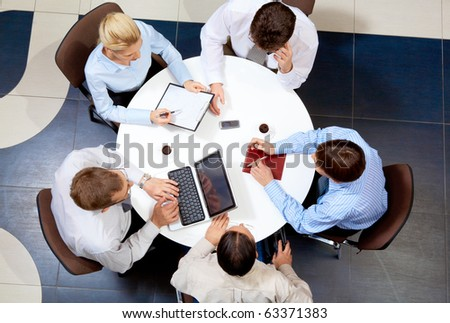 Above view of friendly businessteam working together at meeting