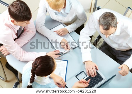 Above view of friendly workteam discussing business plan