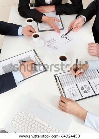 Above view of friendly workteam working with documents at business meeting