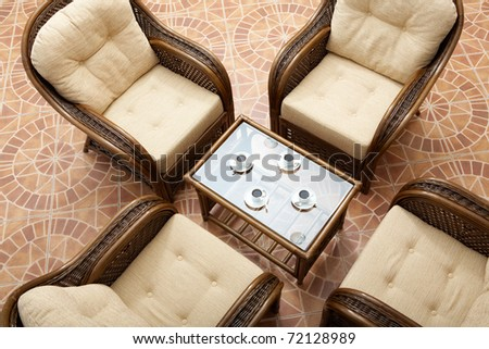 Above view of glass table surrounded by four brown arm chairs