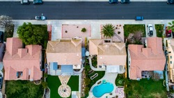 Above view of homes and neighborhoods in the Temecula and Murrieta California in Riverside county with pools, solar panels and tops of roofs with green trees and sun setting light.