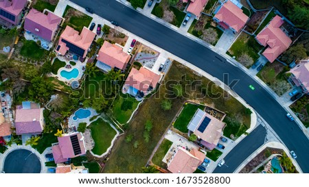 Photo of  Above view of homes and neighborhoods in the Temecula and Murrieta California in Riverside county with pools, solar panels and tops of roofs with green trees and sun setting light.