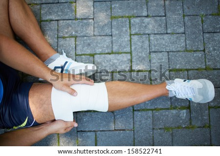 Above view of male bandaging his leg while sitting on pavement