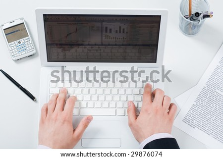 Above view of male hands pushing buttons of laptop with smartphone and papers near by