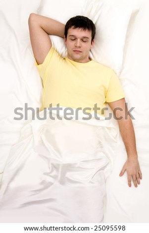 Above view of man with one hand under his head sleeping in cosy bed - stock photo