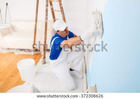 above view of painter with cap and gloves painting a wall with paint roller, wooden vintage ladder and bucket on background