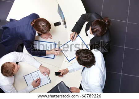 Above view of several business partners discussing business plan