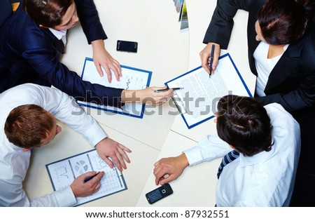Above view of several business partners discussing contract