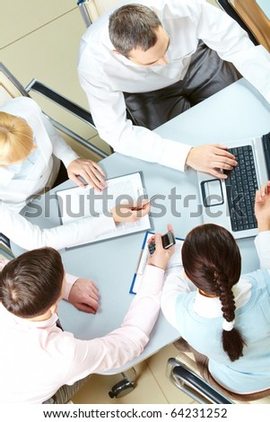 Above view of several business partners interacting at meeting