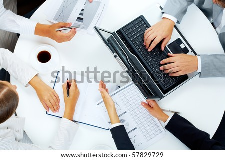 Above view of several business people working at meeting - stock photo