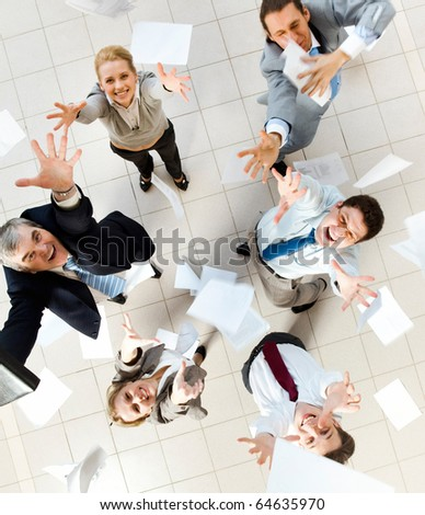Above view of several successful partners throwing papers in joy