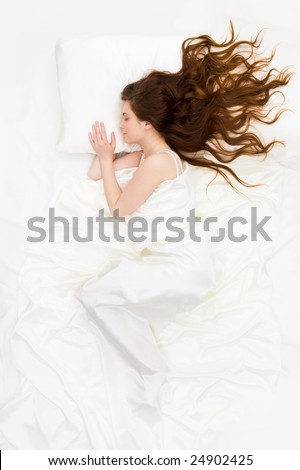 Above view of sleeping woman under white satin sheet