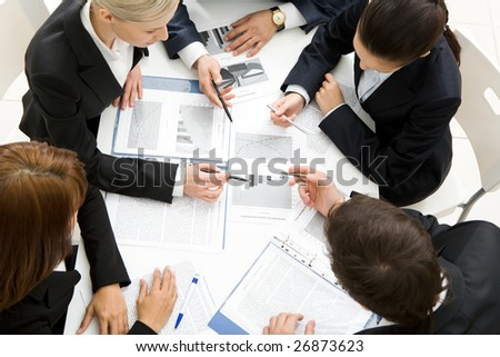Above view of successful workteam discussing new plan at meeting