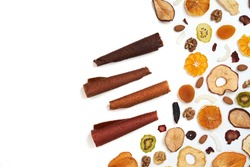 Above view of tasty lozenge with fruits and berries at table and dried fruits kiwi, orange, apple, apricot and bananas on white background. Concept of healthy assorted dried fruit for snacks.