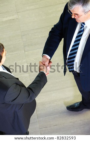 Above view of two managers shaking hands - stock photo