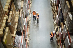 Above view of warehouse workers group in aisle between rows of tall shelves full of packed boxes and goods