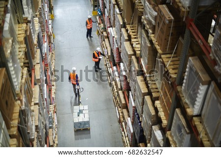Above view of warehouse workers moving goods and counting stock in aisle between rows of tall shelves full of packed boxes