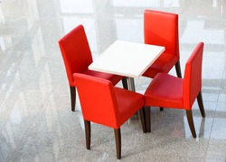Above view of white table with four red chairs near by.