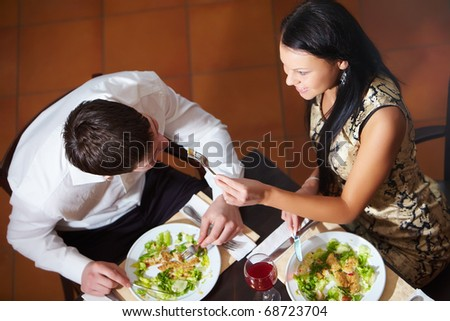 Above view of woman and man eating in cafe