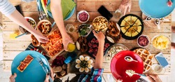 Above view of wooden trendy table full of friends people and home made food to celebrate and stay together having fun in friendship - concept of caucasian men and women mixed ages