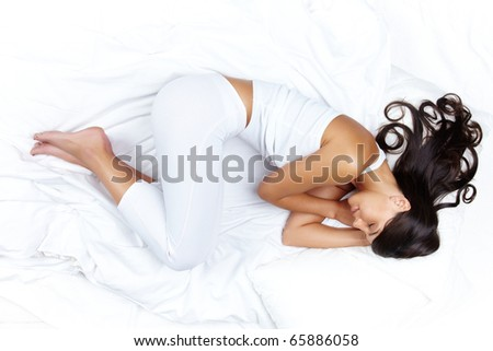 Above view of young beautiful woman in white clothes sleeping in bed