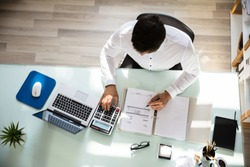 Above view of young businessman calculating invoice