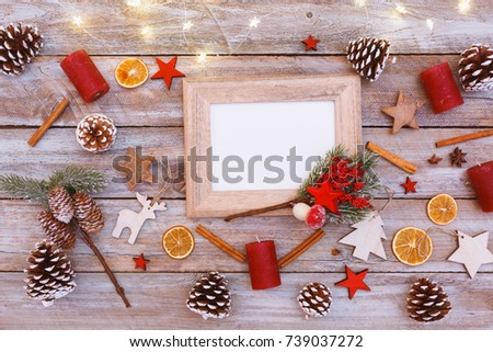 Above view on chaotic arranged christmas and winter decorated table with image photo frame and light chain shining, including copy space
