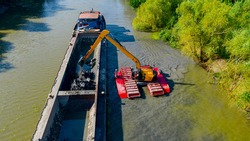 Above view on excavator dredge is dredging, working on river, canal, deepening and removing sediment, mud from riverbed in a polluted waterway.