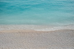 Above view on sunny beach with clear turquoise water and pebbles. Vibrant blue sea with tranquil waves. Minimal trendy seascape background. Relaxation, summer vacation concept.