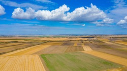 Above view over agricultural fields, cultivated plots in harvest season, blue sky with white fluffy clouds their shadows are on the ground.