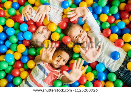 Above view portrait of three happy little kids in ball pit smiling at camera raising hands while having fun in children play center, copy space #1125288926