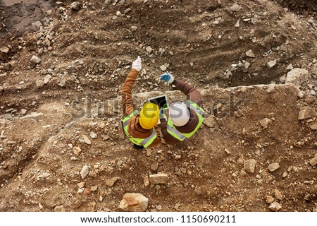 Above view shot of two industrial  workers wearing reflective jackets and hardhats standing on mining worksite outdoors using digital tablet, copy space