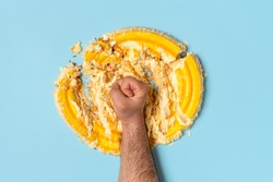 Above view with a man's fist smashing a cake. Concept for dieting with an orange whipped cream cake destroyed by a man, top view.
