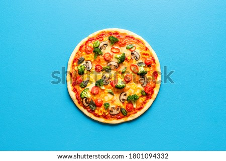 Above view with a whole pizza primavera isolated on a blue colored background. Vegetarian pizza with broccoli, champignons, tomatoes, corn and pepper. Foto stock ©