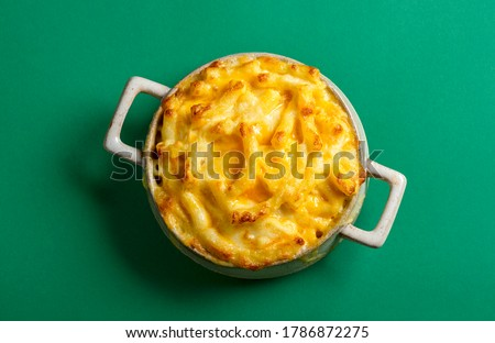 Above view with cooked mac and cheese in a ceramic tray, isolated on a green colored background. Tasty homemade food with macaroni and cheese. Stock fotó ©
