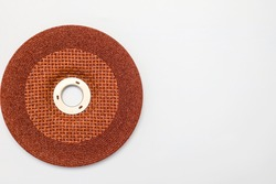 Abrasive wheel, grinding disc of orange, brown color, isolated on white background. Abrasive materials, discs, tools close-up
