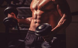 Abs and biceps. Muscular man with dumbell. Strong bodybuilder in the gym. Muscular man on gym background with dumbbell.