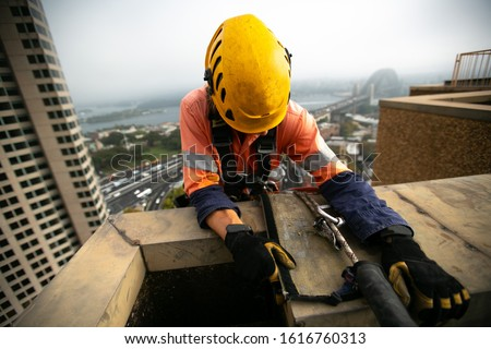 Abseiler inspector wearing yellow head fall protection safety helmet fall body harness, climbing over the edge while his rope and safety backup device on the rope protection SYD high rise building