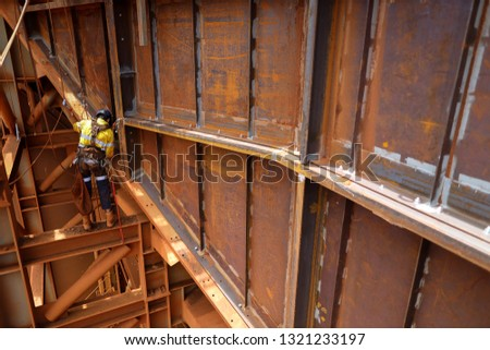 Abseiler rope access wearing a safety fall body harness protection, helmet sanding in fall restraint position performing oxy acetylene cutting metal beam construction site, Sydney, Australia