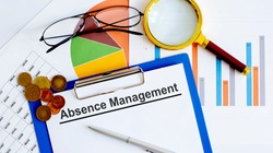 ABSENCE MANAGEMENT Business reports, blank paper , data tables and charts,magnifier,coins - directly above view of office table