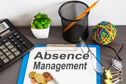 ABSENCE management written on paper with office tools