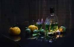 Absinthe, an alcoholic drink. Creative stimulator of a sober lifestyle. Two glasses of hot absinthe next to a green bottle shaped like a skull and fruit.