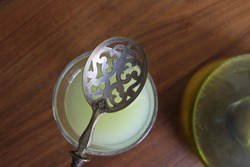 Absinthe in a traditional glass with a spoon photographed from above on a wooden background