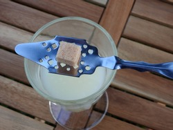 Absinthe louche (opalescent shade of milky green) in a traditional glass, traditional silver spoon and a single square brown sugar cube on top placed on a wooden table