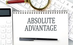 ABSOLUTE ADVANTAGE . Text on notepad with calculator and keyboard,business
