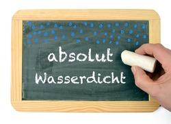 absolute waterproof in german absolut wasserdicht, written on a chalkboard