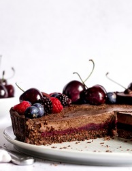 Absolutely delicious, freshly made and cut to be served vegan chocolate cherry tart with nutty chocolate base, layer made of sweet and sour cherries and topped with a layer of rich, velvety chocolate