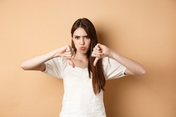 Absolutely no. Disappointed young woman frowning and showing thumbs down, express dislike and negative emotions, bad feedback, standing on beige background