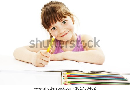 Absorbed little girl drawing with colorful pencils isolated on white background