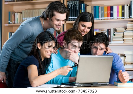 Absorbed young students watching at laptop and study together at college library